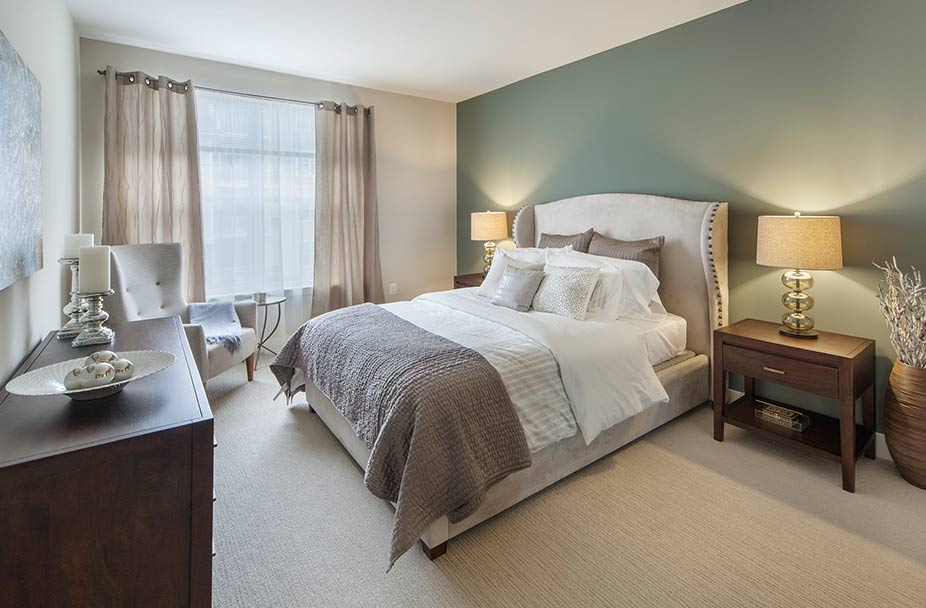 furnished bedroom with gray carpet, green walls, queen bed with white linens and wood cabinetry at Parc apartments in Plymouth Meeting, PA