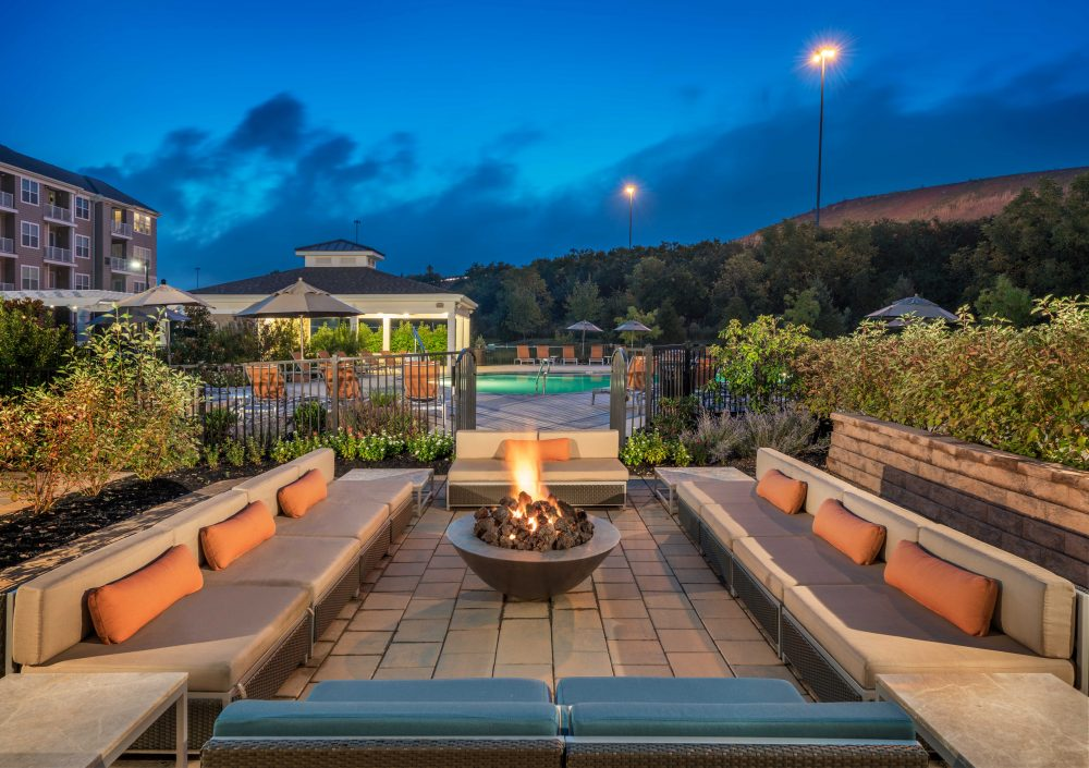 close up view of outdoor lounge with lit fire pit facing pool area at Parc apartments in Plymouth Meeting, PA