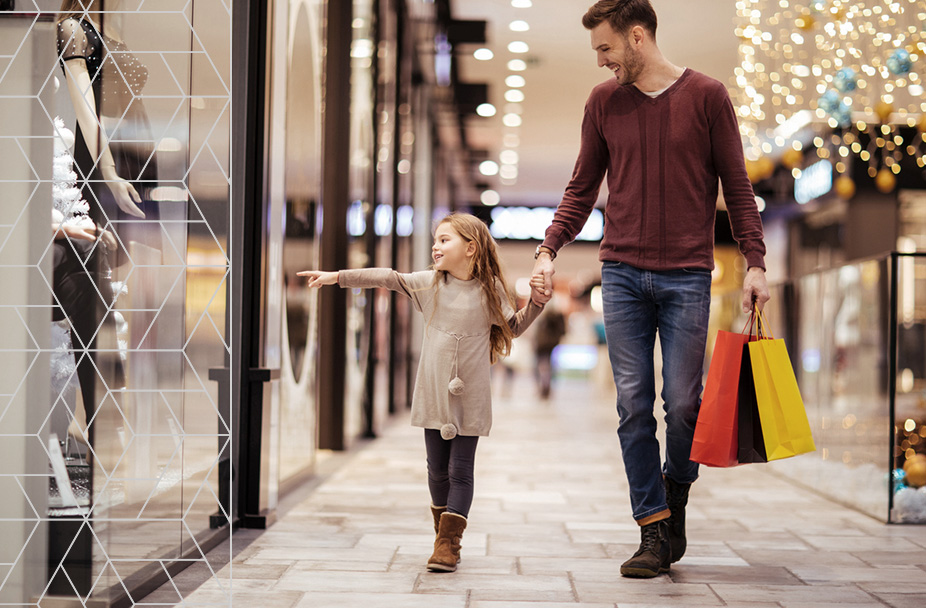 photo of man holding little girl's hand while shopping in a mall