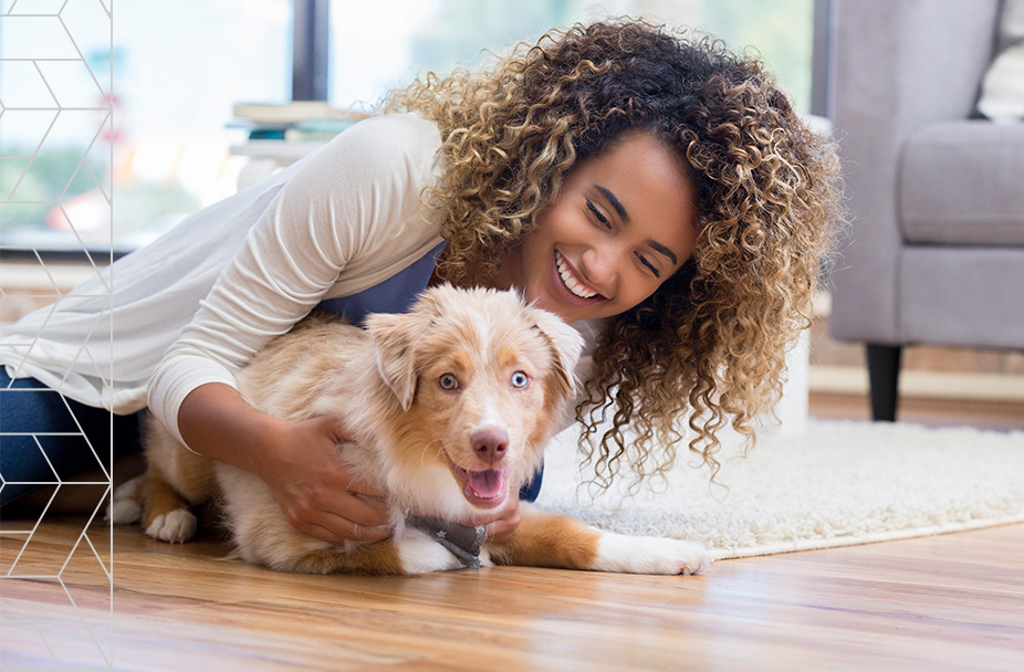 photo of smiling woman holding puppy on floor